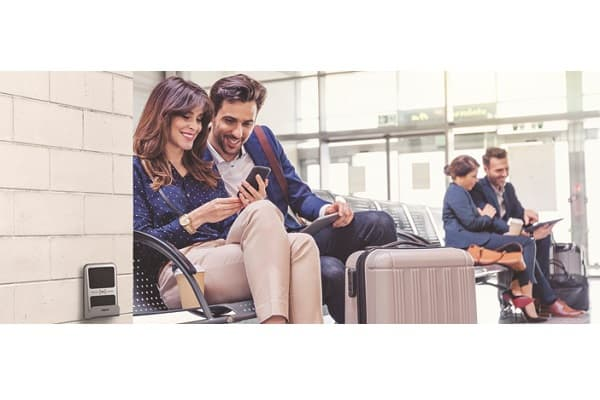 Young businessman and businesswoman sitting on bench at airport lounge using mobile phone, with people in background. People waiting for flight.