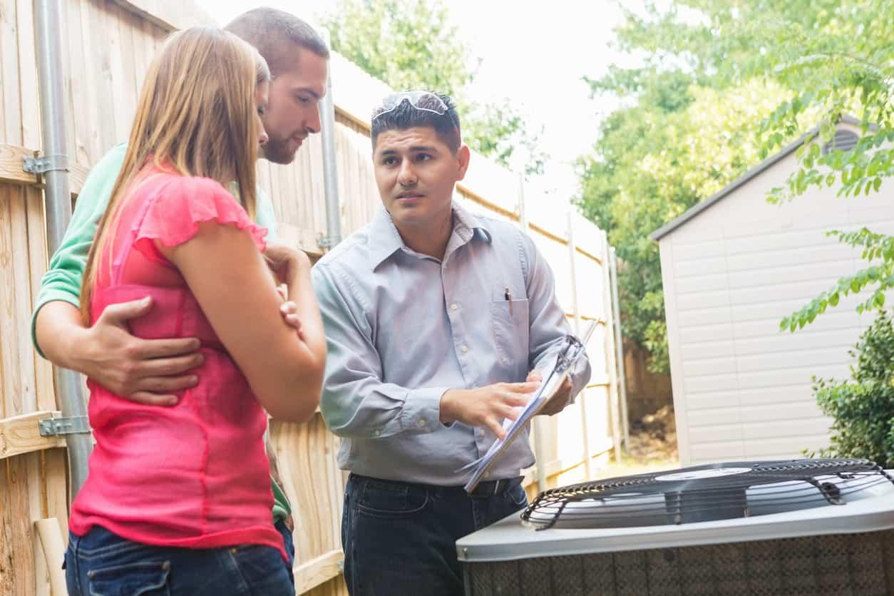Air Conditioner repairman explaining cost of repairs to homeowners